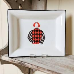 racing silks on a rectangular dis on a shelf